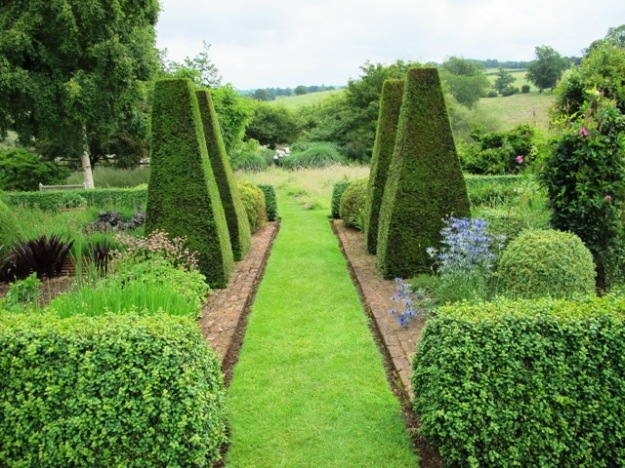 Clipped accent plants give form in this garden which has predominantly loose herbaceous plantings and grassy meadows. Pettifers near Stratford on Avon.