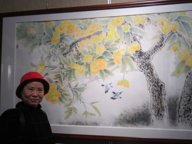 Artist Xinger Li with her lovely painting titled (in English) 'Chinese Camellia with Dense Dew""